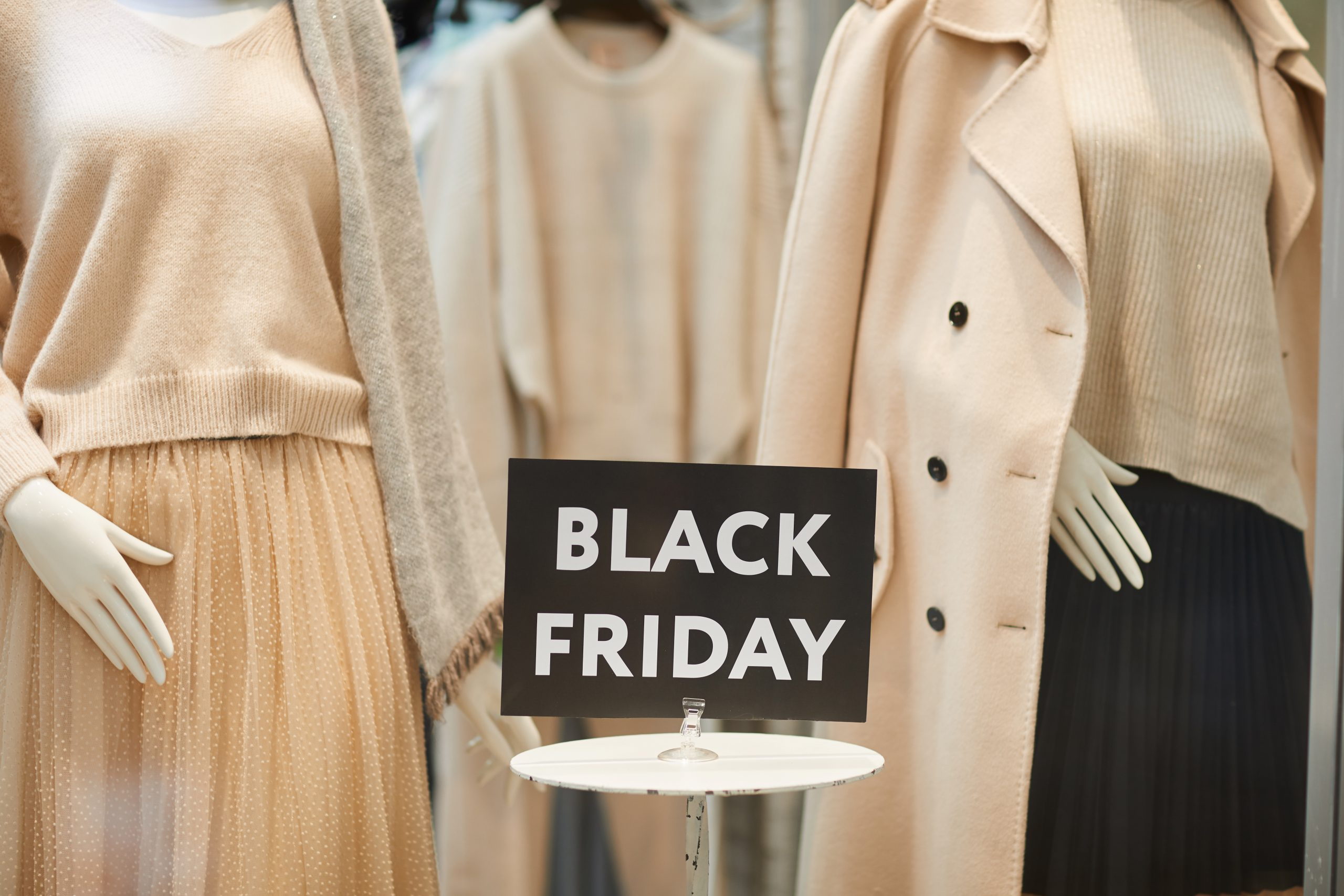 Close up of Black Friday sale sign on window display with autumn clothes in shopping mall, copy space
